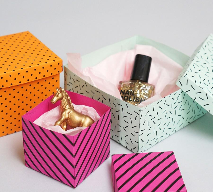 Pyssel med askar i papper med grafiska mönster.