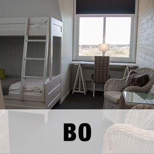 """Bild på ett av Golfarenans hotellrum med texten """"BO""""."""