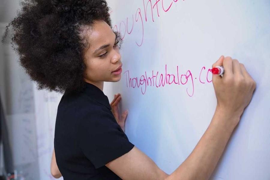 Lärare som skriver med en penna på en whiteboard-tavla