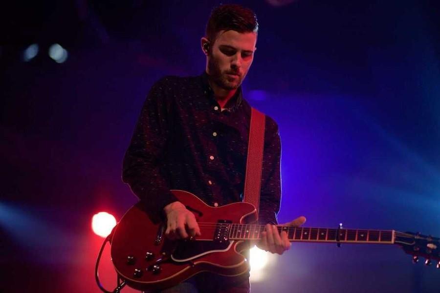 Artist som står på scen och spelar på en röd gitarr