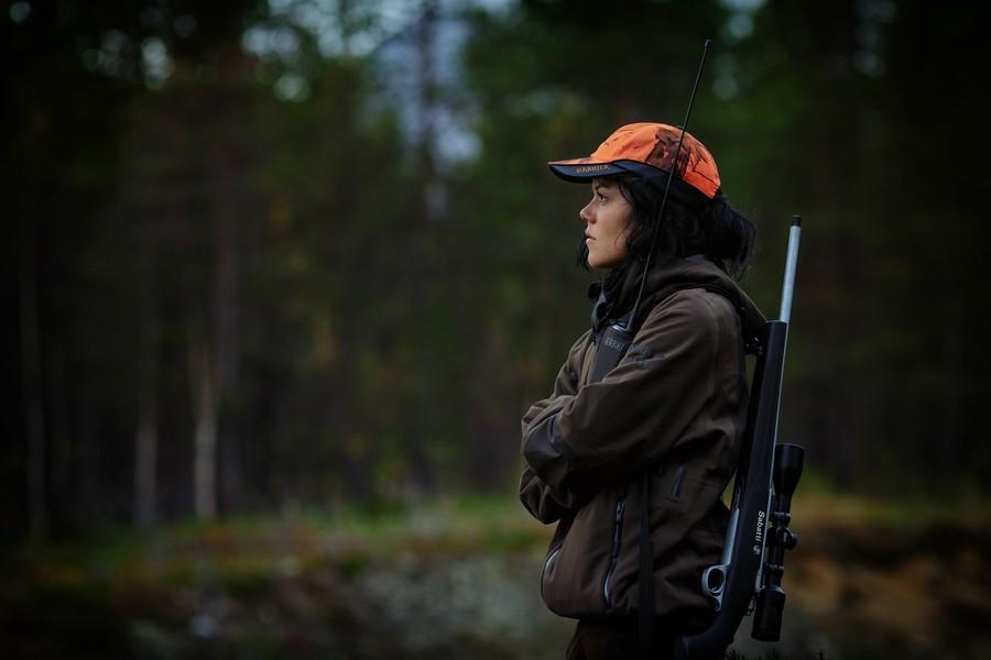 Kvinna med orange mössa som står i en skog med ett gevär på ryggen