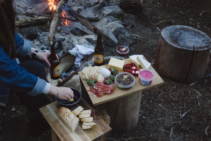 uppdukade delikatesser på en träbricka med en levande brasa i bakgrunden