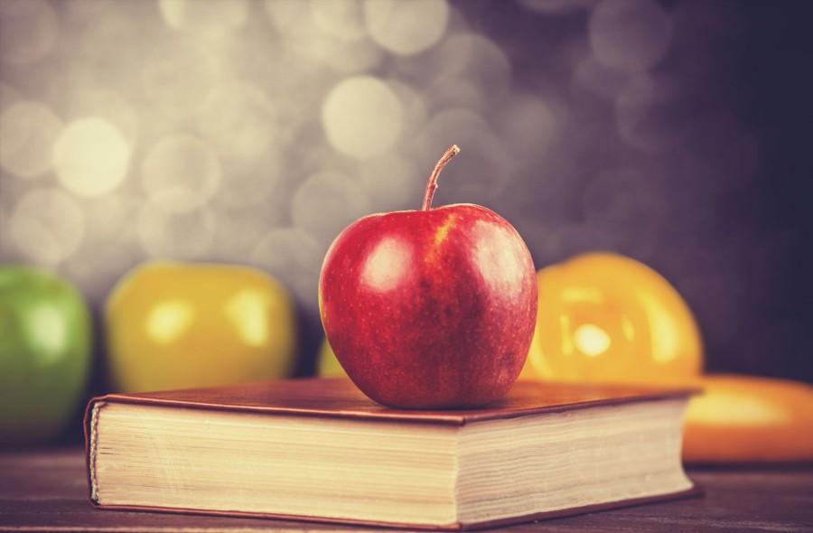 ett rött äpple ligger ovanpå en stängd bok
