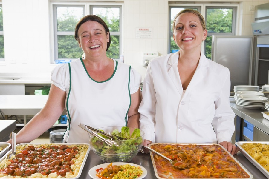 i ett tillagningskök står två glada kvinnor och ler mot kameran. På bordet framför finns fat med mat